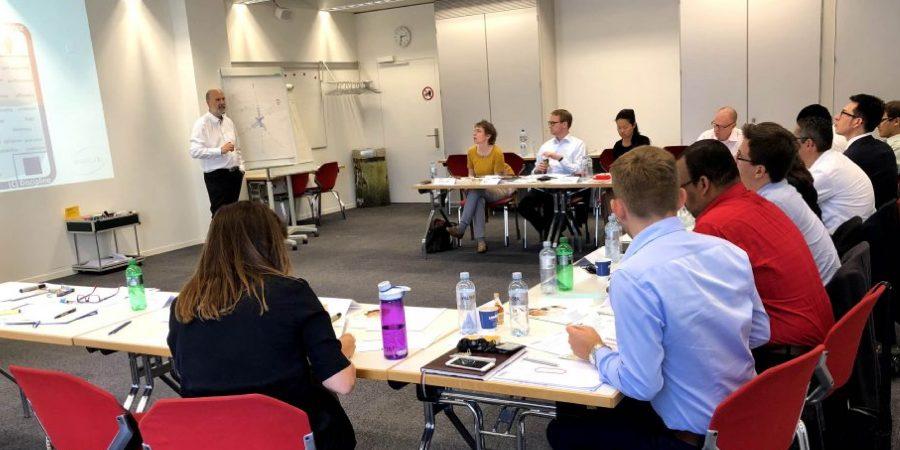 Teilnehmer sitzen im Raum eines Präsentationstrainings