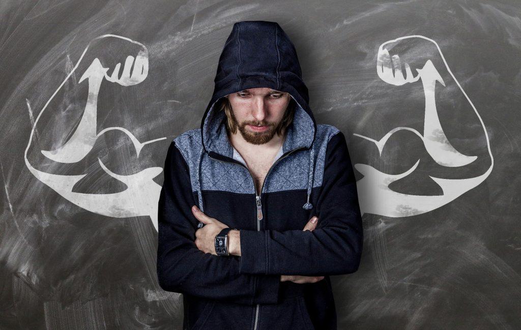 Mann verschränkt vor seinem Körper die Arme negative Körpersprache