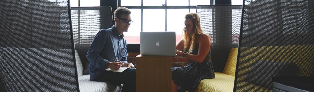 Meeting zwischen einer jungen Frau und einem jungen Mann vor einem Macbook